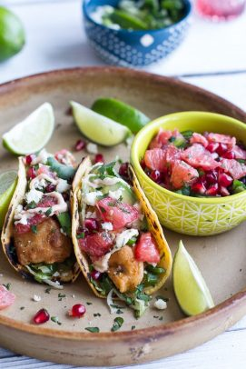 Two Baja fish tacos with a bowl of grapefruit salsa