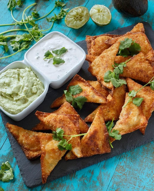 Southwestern Wontons on a plate with avocado and lime crema dipping sauces