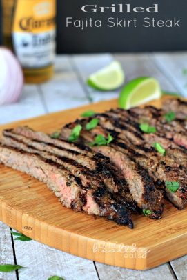 Grilled Fajita Skirt Steak sliced on a cutting board with fresh herbs and lime wedges