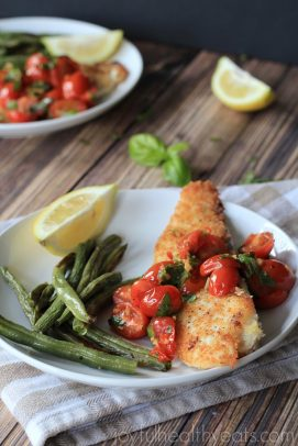 Breaded fish with tomatoes and green beans on a plate