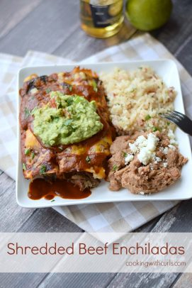 Shredded beef enchiladas topped with guacamole on a plate with rice and refried beans