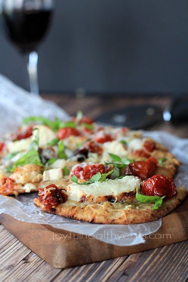 Side view of Grilled Chicken Margherita Pizza on parchment paper