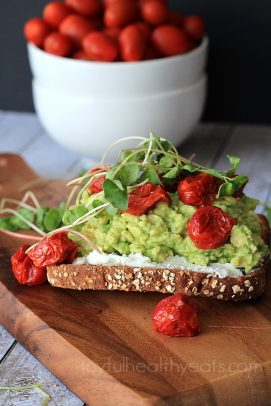 Toast with goat cheese, mashed avocado, roasted cherry tomatoes and microgreens