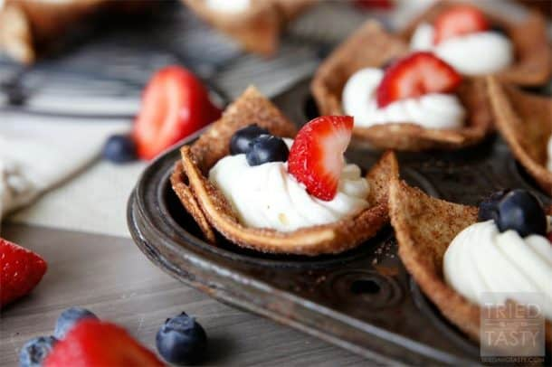 A muffin tin with red, white and blue tortilla cups topped with whipped cream and fresh berries