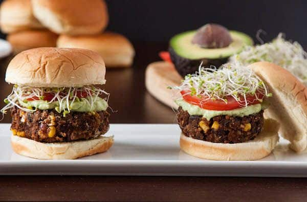 Chipotle Black Bean Freekeh sliders on bun with avocado spread, tomato and sprouts
