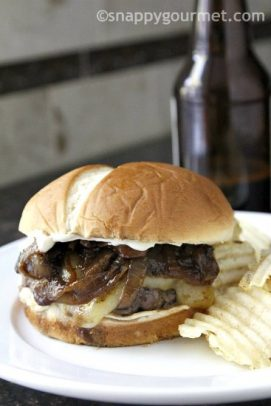 French Onion Beer Burger with bun on a plate with chips