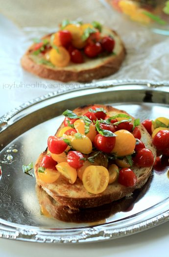 The perfect Summer appetizer to munch on! Fresh Tomato Bruschetta tossed with basil, garlic olive oil, served on toasted bread, and drizzled with a sweet balsamic reduction. OMG! | joyfulhealthyeats.com #recipes