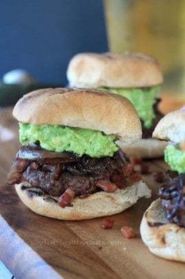 Slider burgers topped with caramelized onions and mashed avocado on a bun