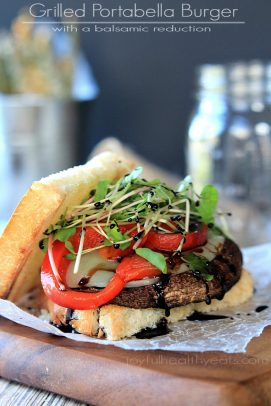 Grilled portabella burger with red peppers and greens on a bun