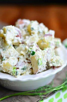 A white bowl of parmesan herb potato salad