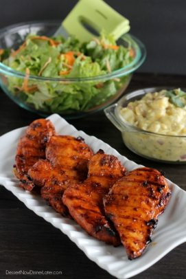 Spicy honey grilled chicken on a platter with a bowls of green salad and potato salad