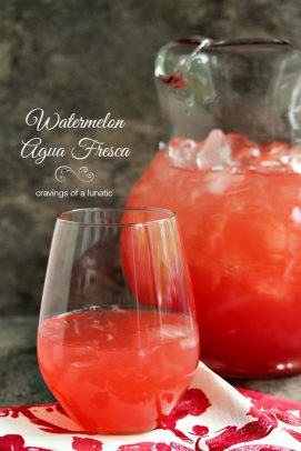 A clear pitcher and a glass of watermelon agua fresca with ice
