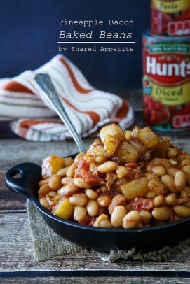 A black bowl of pindapple bacon baked beans