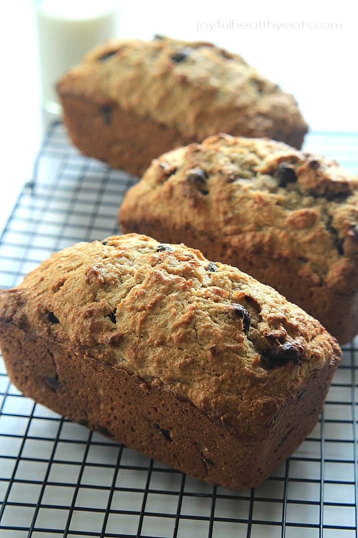 Three loaves of Coconut Pecan Chocolate Chip Banana Bread on a cooling rack