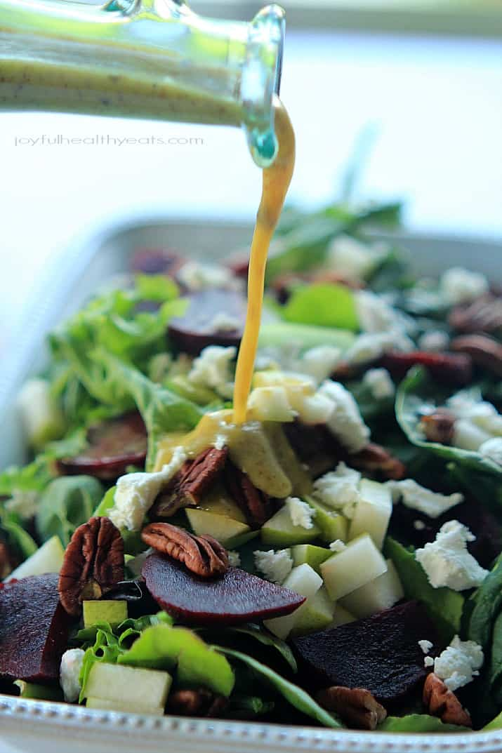 Honey Mustard Vinaigrette being poured over Goat Cheese Asian Pear & Beet Salad