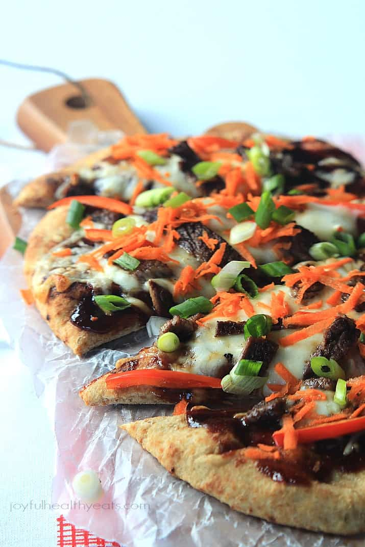 A Grilled Short Rib Flatbread on a Wooden Surface Covered in Wax Paper