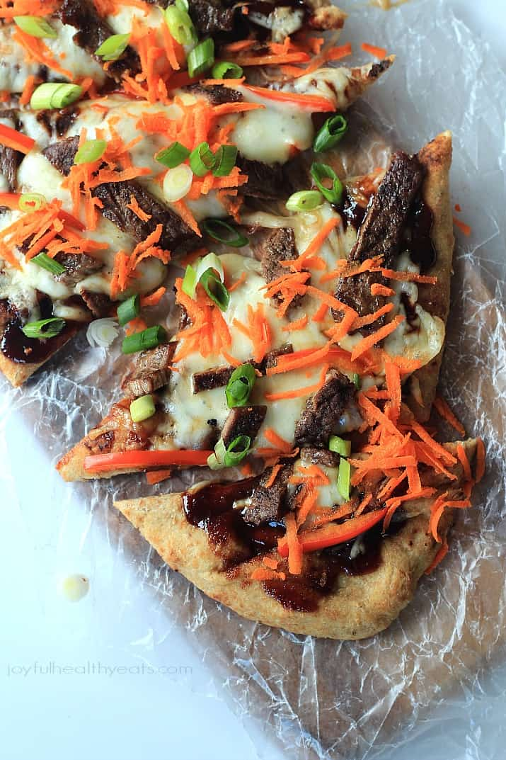 Four Slices of Short Rib Pizza Topped with Shredded Carrots