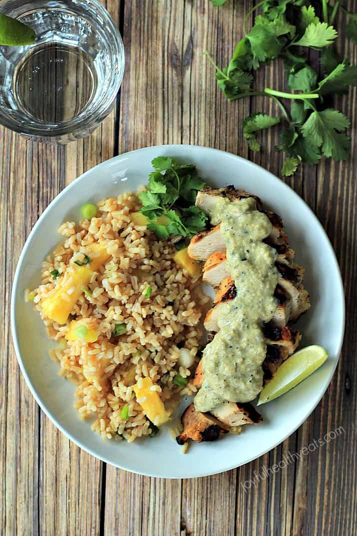 Top view of Grilled Chicken with Tomatillo Sauce and pineapple rice on a plate