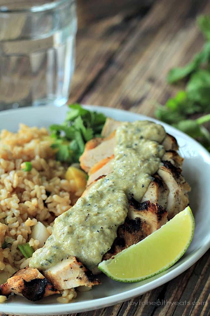 Close-up of Grilled Chicken with Tomatillo Roasted Poblano Cream Sauce and pineapple rice on a plate