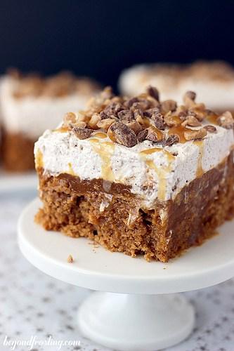 A Piece of Double Pumpkin Poke Cake on a White Cake Stand
