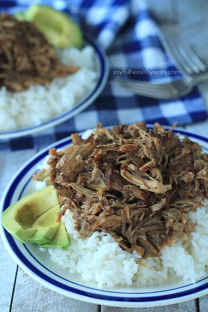 Close up view of a plate of Honey Balsamic Pulled Pork over white rice with sliced avocado