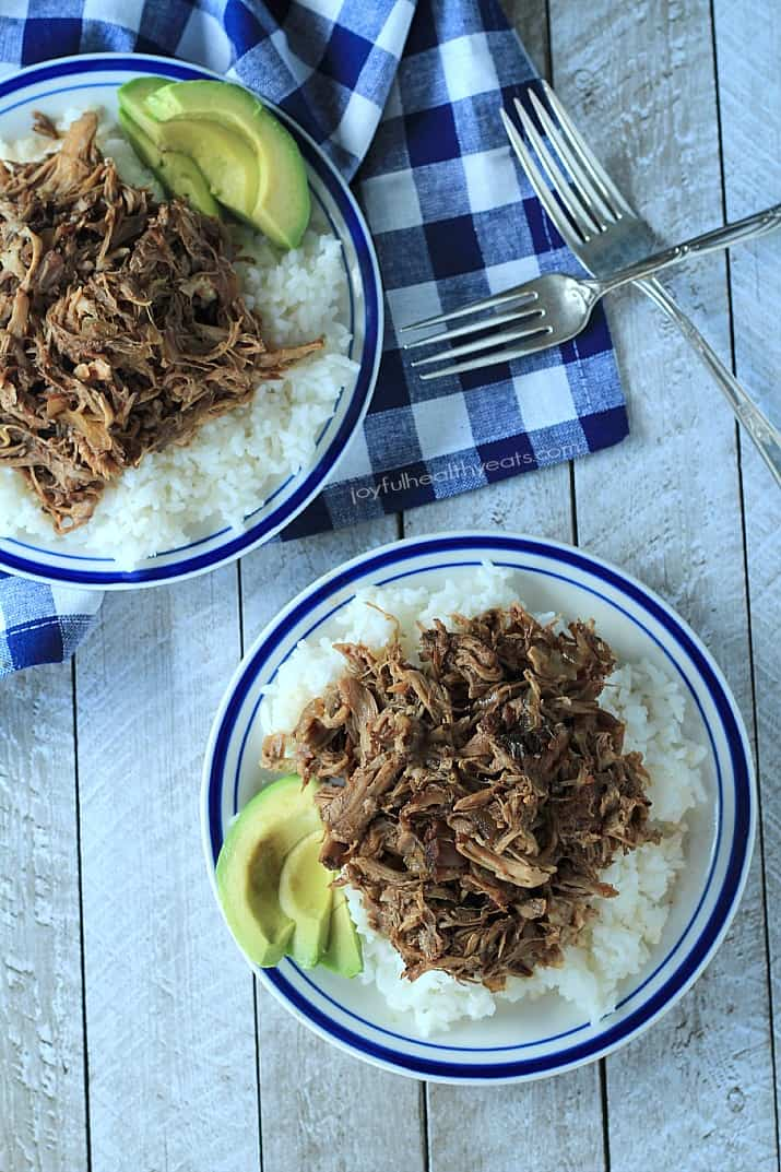 Top view of two plates of Honey Balsamic Pulled Pork over white rice with sliced avocado