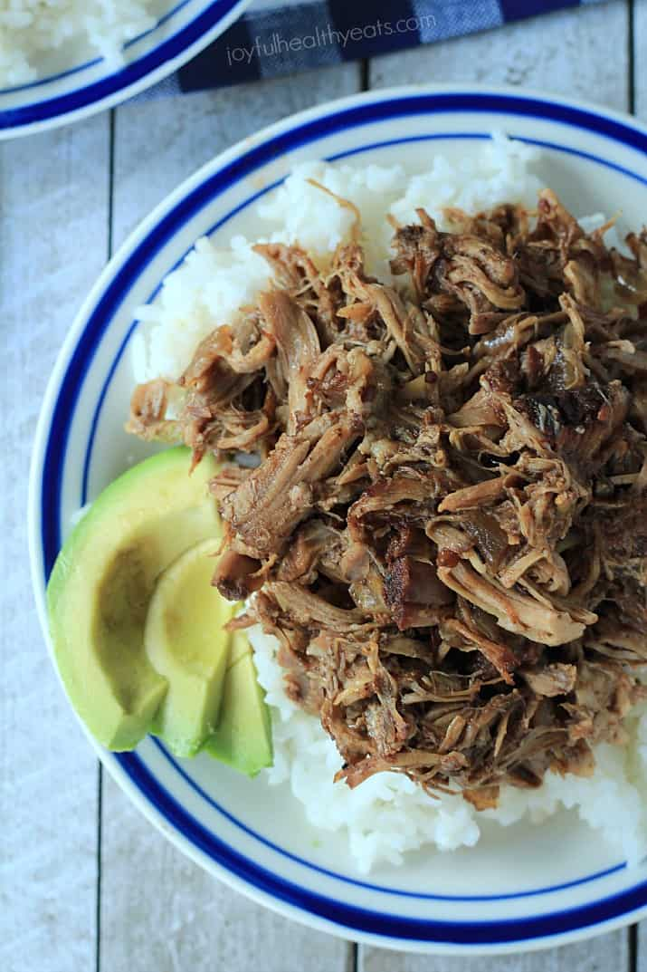 Top view of a plate of Honey Balsamic Pulled Pork over white rice with sliced avocado