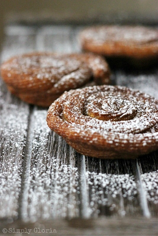 Three Mini Pumpkin Funnel Cakes Topped with Powdered Sugar