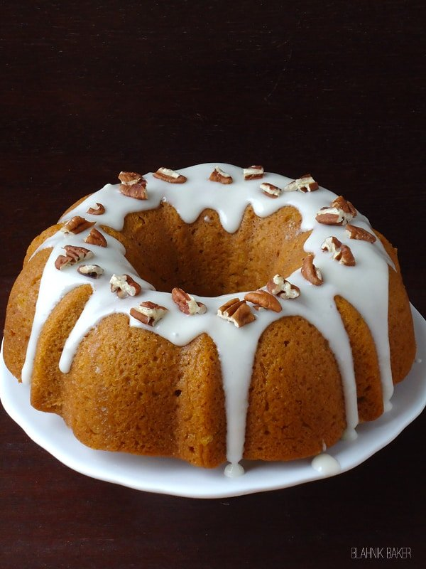 An Iced Pumpkin Bundt Cake with Bourbon on a Plate in Front of a Black Background