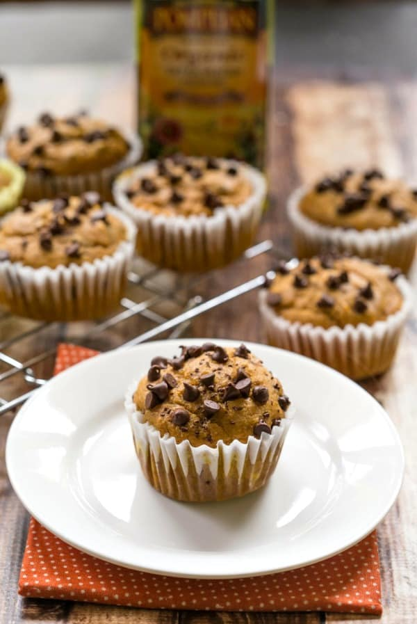A Pumpkin Chocolate Chip Muffin on a Plate in Front of Five Other Muffins