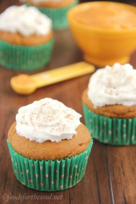 Three Butterscotch Filled Pumpkin Cupcakes with Whipped Cream Beside a Bowl of Pumpkin Puree