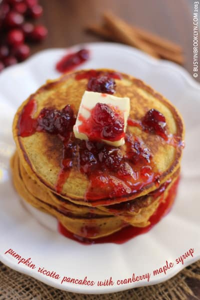 A Stack of Pumpkin Ricotta Pancakes Topped with Cranberry Syrup and a Square of Butter