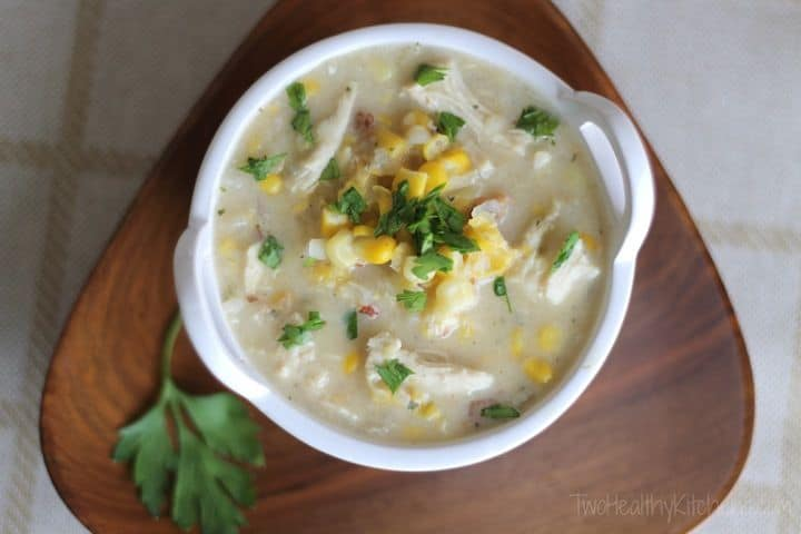 A Crock of Creamy Chicken & Corn Chowder on a Wooden Plate