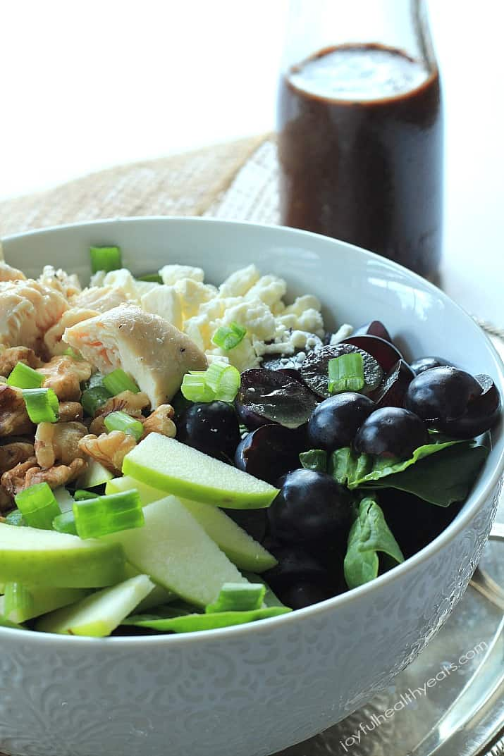 Chicken Feta Walnut Grape Chopped Salad in a bowl alongside a carafe of Balsamic Vinaigrette