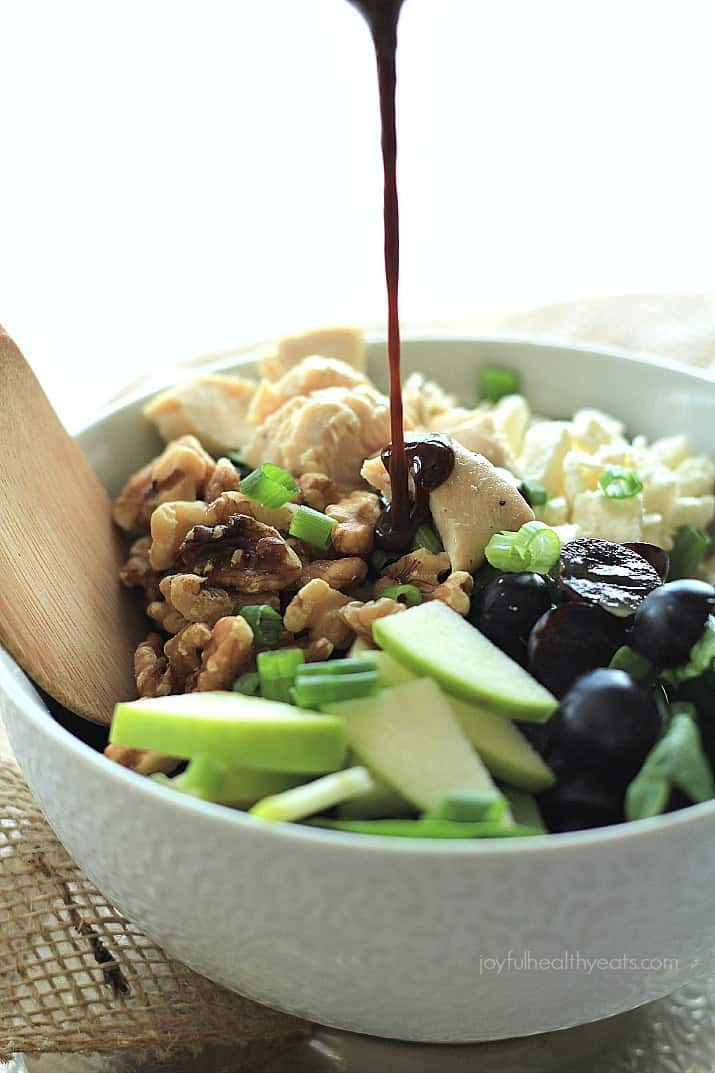 Drizzling Vinaigrette Over a Chicken Feta Walnut Grape Chopped Salad