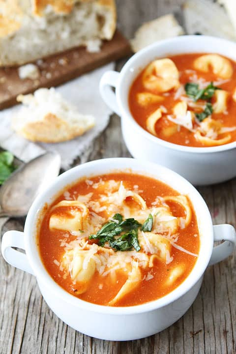 Two Mugs of Creamy Tomato Tortellni Soup on a Picnic Table