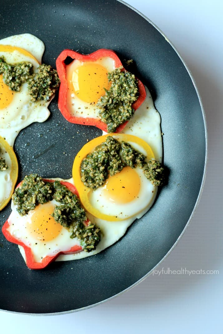 Top view of Egg in a Hole with Basil Pesto and bell pepper rings in a skillet