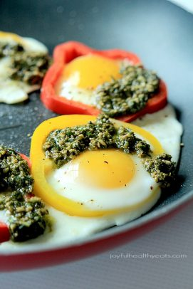 A skillet of Bell pepper rings filled with an egg and pesto