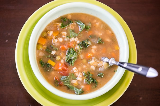 A Bowl of Winter Vegetable Soup with a Metal Spoon Inside