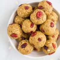 a bowl filled with pumpkin energy balls with cranberries