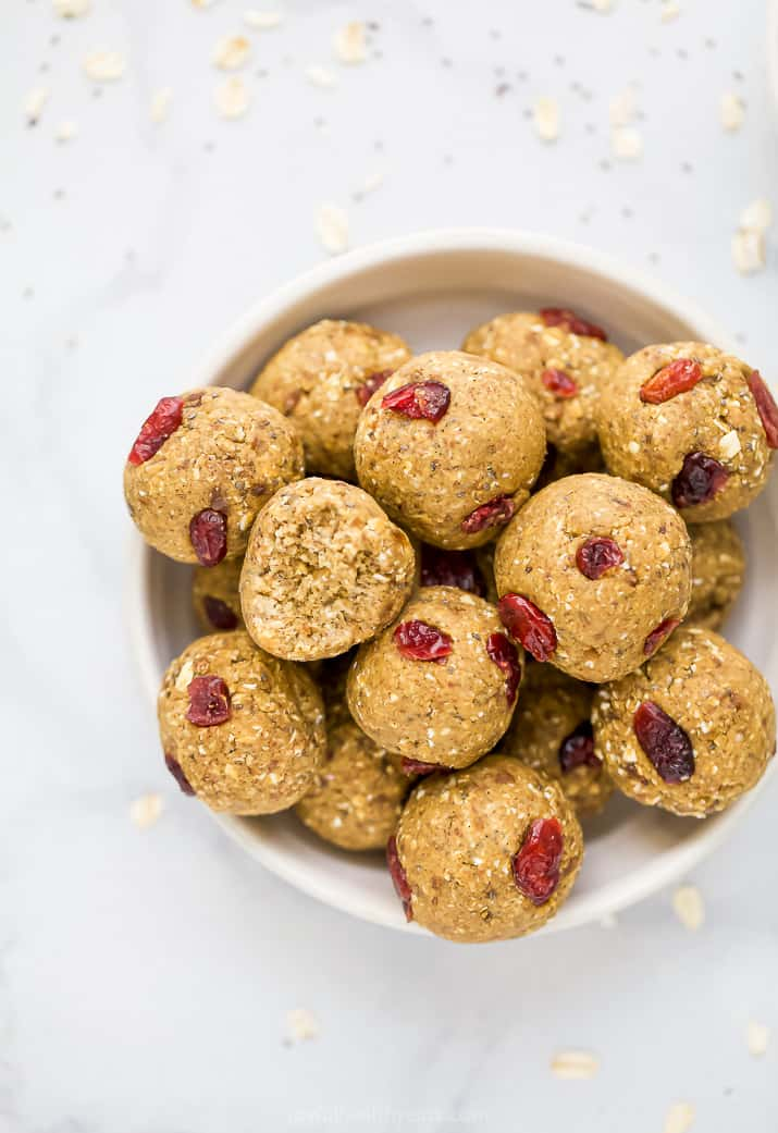 a bowl filled with pumpkin protein balls with cranberries