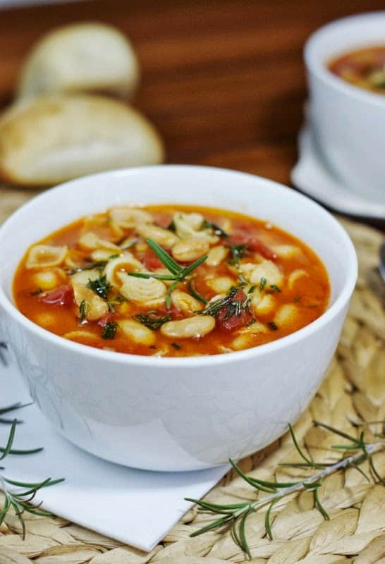 A Bowl of Pasta e Fagioli in Front of Two Rolls of Bread