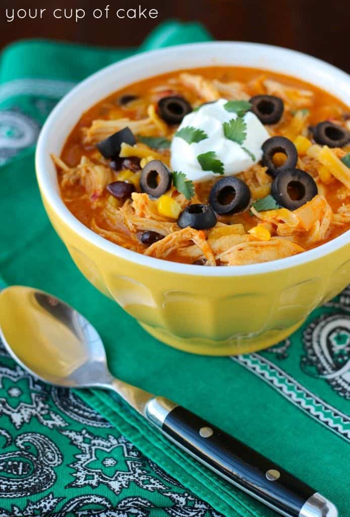 A Yellow Container of Crock Pot Chicken Enchilada Soup Topped with Sour Cream