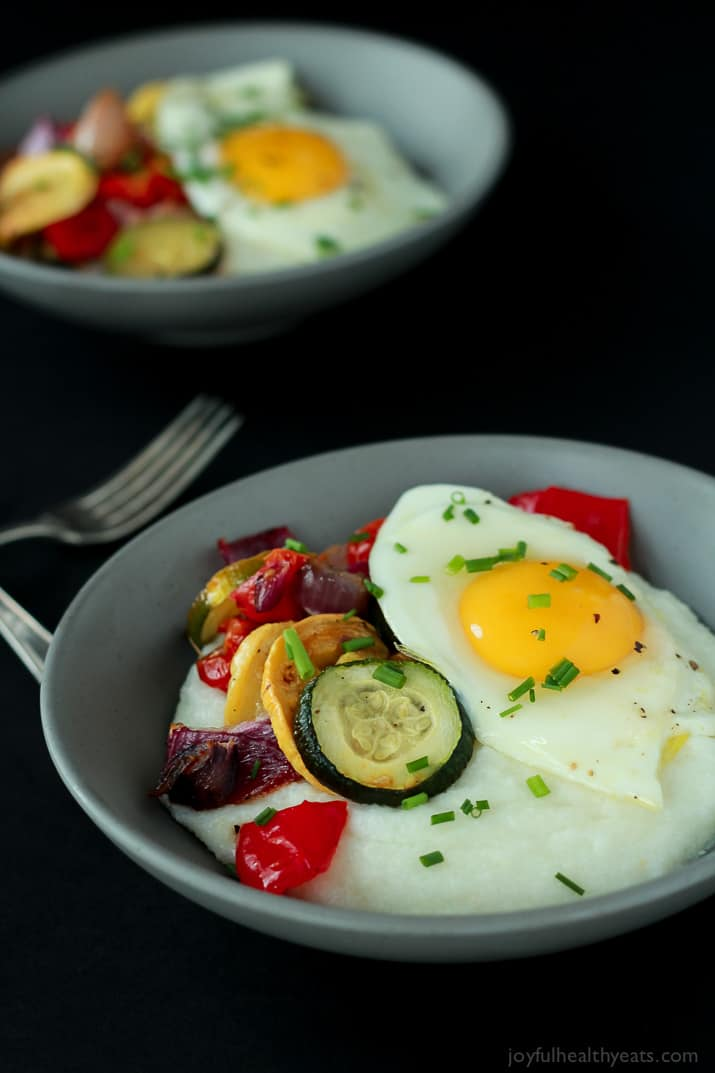 Two Bowls of Grits with Eggs & Veggies Beside Two Forks