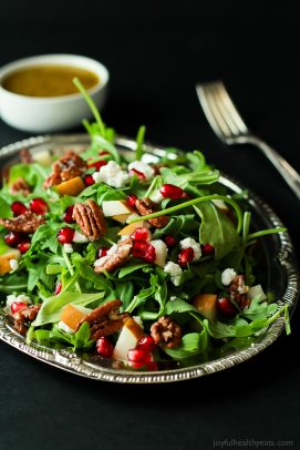 Pomegranate Goat Cheese Candied Pecan Arugula Salad on a silver plate