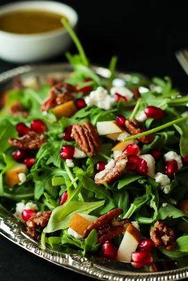 Pomegranates, Goat Cheese, and Candied Pecans on an Arugula Salad in a silver bowl