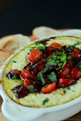 Baked goat cheese dip in a ramekin topped with tomatoes and herbs
