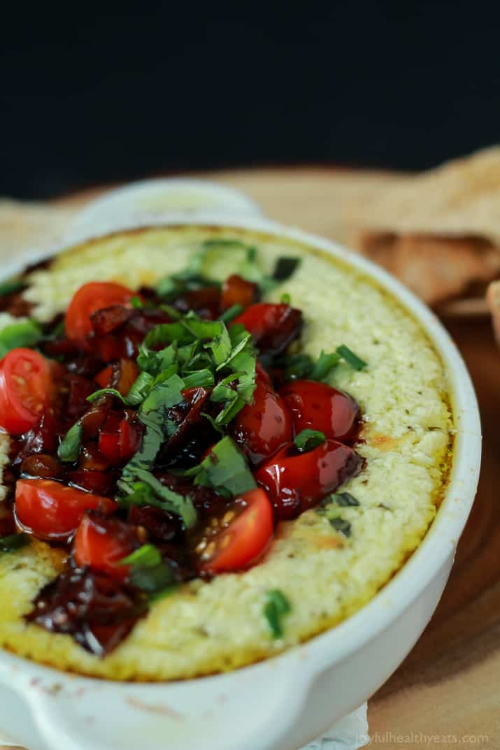 A crock of Baked Goat Cheese Dip topped with balsamic bruschetta