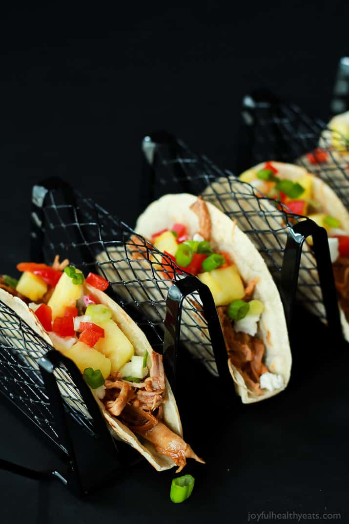Hawaiian Pork Tacos filled with sweet pulled pork, fresh pineapple, red peppers, and goat cheese in a taco holder rack