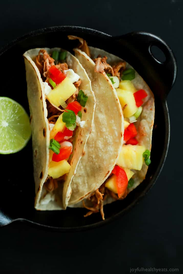Top view of two Hawaiian Pork Tacos filled with sweet pulled pork, fresh pineapple, red peppers, and goat cheese
